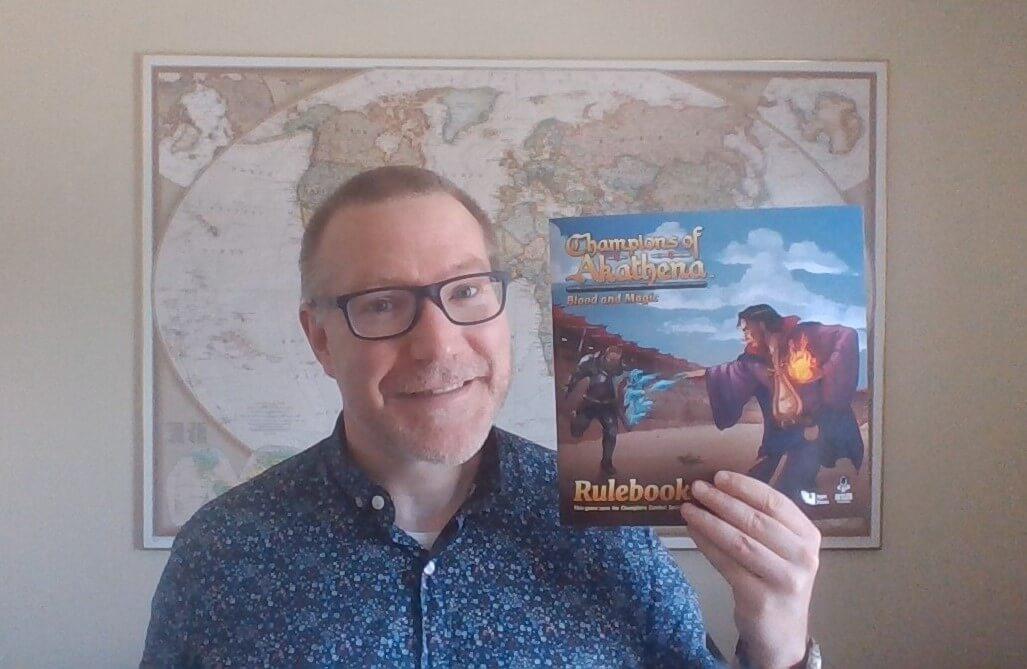 PK 243: Launching A Board Game on Kickstarter 11 Holding Rulebook